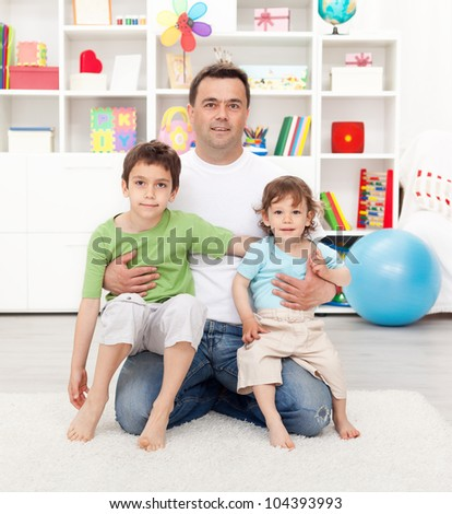Proud father with his sons sitting on his lap at home - stock photo