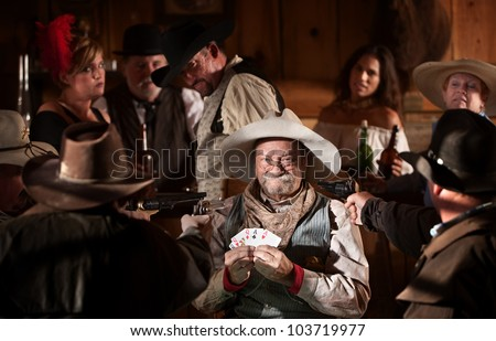 Proud gambler holds winning cards with jealous players - stock photo