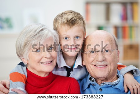 Proud happy elderly grandparents posing with their adorable little grandson hugging them from behind grinning playfully at the camera - stock photo