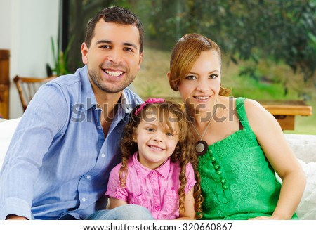 Proud happy hispanic parents posing with little cute girl wearing pink clothes in front of window garden background. - stock photo