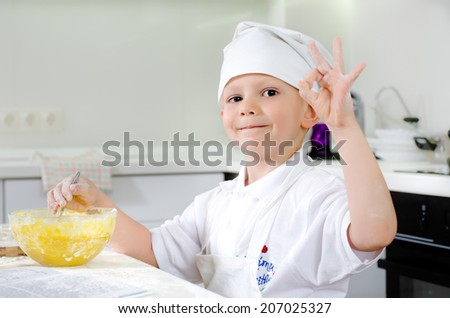 Proud little boy baking in the kitchen wearing a chefs uniform giving a perfect gesture with a big smile as he stirs ingredients in the bowl - stock photo