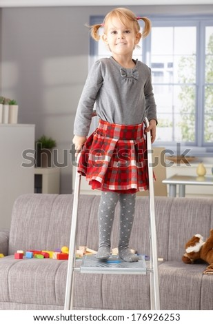 Proud little girl smiling happily on top of ladder. - stock photo