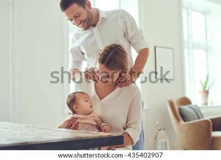 Proud mother and father smiling at their newborn baby daughter at home - stock photo