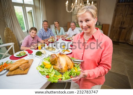 Proud mother showing roast turkey at home in the living room - stock photo