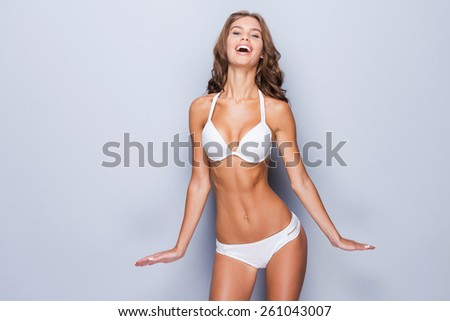 Proud of her perfect body. Attractive young brown hair woman in white lingerie posing against grey background and smiling - stock photo