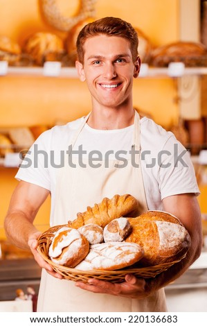 Proud of his baked goods. Handsome young man in apron holding basket with baked goods and smiling while standing in bakery shop - stock photo
