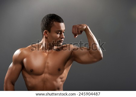 Proud of his fit body. Closeup portrait of young shirtless African man showing his bicep with tattoo while standing against grey background  - stock photo