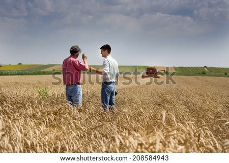 Proud peasant and businessman talking on wheat field during harvesting - stock photo