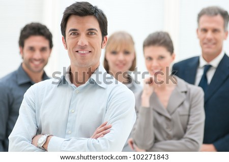 Proud smiling businessman standing with his colleagues at office - stock photo