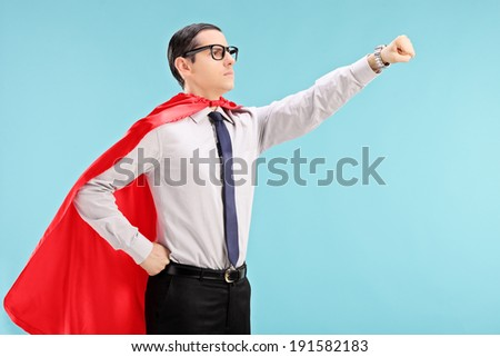Proud superhero with gripped fist on blue background - stock photo