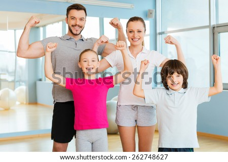 Proud to be strong and healthy. Happy sporty family showing their biceps and smiling while standing close to each other in sports club  - stock photo