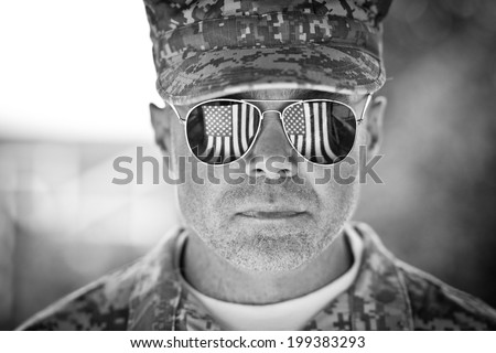 Proud us army soldier with american flag in sunglasses reflection. black and white - stock photo