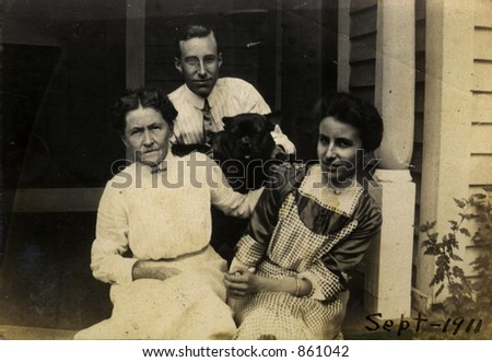 Proud vintage mother with her adult children and the family pet.  Original Circa 1911 print has scratches, stains, artifacts, fading and solarization qualities. - stock photo