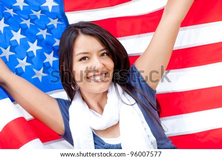 Proud woman with the American flag and smiling - stock photo