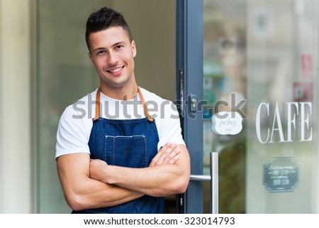 Proud young cafe owner in doorway  - stock photo
