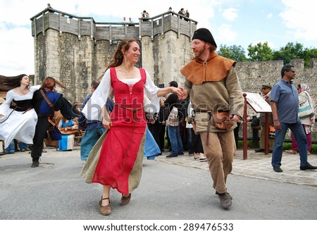 PROVINS, FRANCE - JUNE 23, 2012: People dancing and whirling in medieval costume during the traditional Medieval festival. Medieval town of Provins is UNESCO World Heritage Site. - stock photo