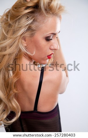provocative female with sexy white lace lingerie and voluptuous body, in erotic pose showing her sexy back - stock photo