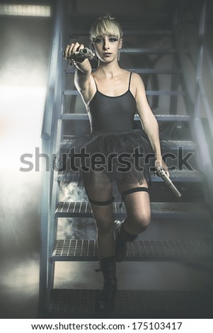 Provocative. Young blonde woman with black dress holding a gun. - stock photo