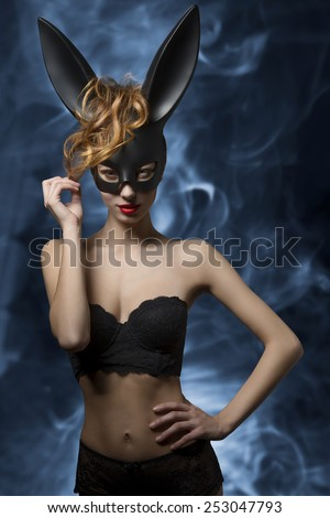 Provocative young woman with dark bunny ears posing in easter glamour portrait with lace lingerie and perfect body  - stock photo
