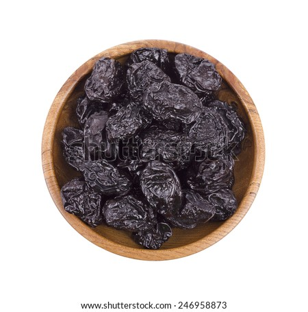 Prunes in wooden bowl isolated on white - stock photo