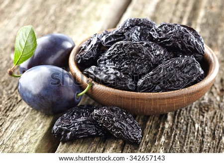 Prunes on a wooden background - stock photo