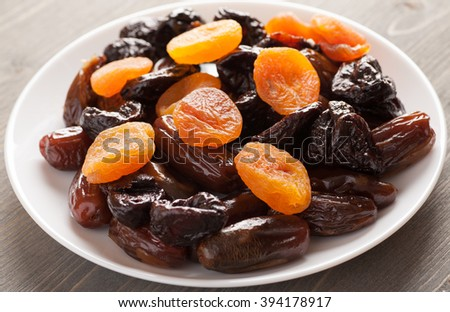 Prunes with dried apricots and dates in a white plate, closeup shot, selective focus - stock photo