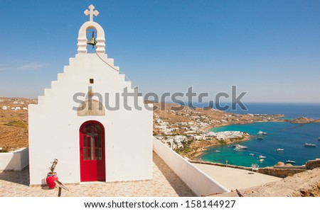 Psaru beach of Mykonos, Greece and church. Sunny with blue sky and crystal clear water - stock photo