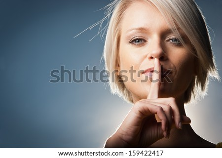 Psst - a beautiful woman making a shushing gesture raising her finger to her lips as she asks for silence or secrecy, studio portrait on grey with copy space. - stock photo