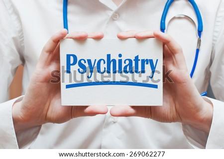 Psychiatry written on a card in doctor hands - stock photo