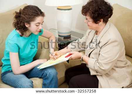 Psychologist giving a teen girl an agreement to sign before starting therapy. - stock photo