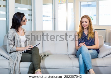 Psychologist talking with happy woman in the office - stock photo