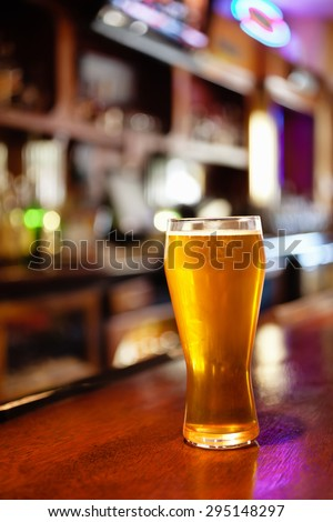 Pub beer glass on a bar counter at a tavern - stock photo