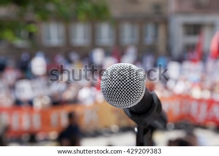 Public demonstration. Protest. Microphone in focus against unrecognizable crowd. - stock photo