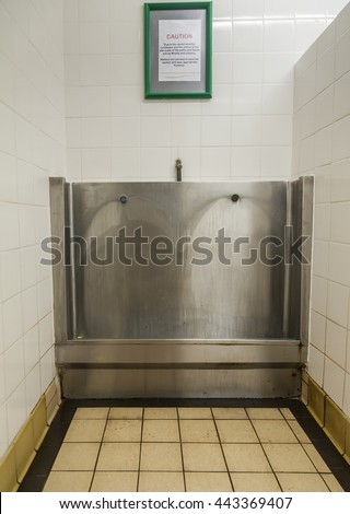 Public men's stainless steel urinal trough in tiled  bay. - stock photo