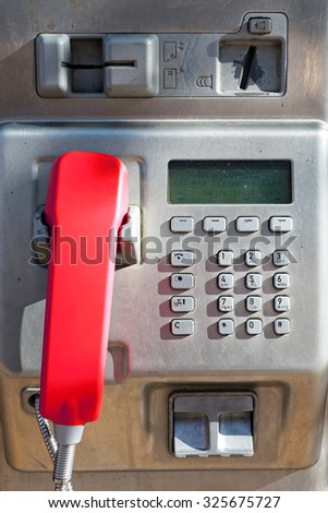 Public phone made from metal with  keypad, coin insertion, card slot and a red handset - stock photo