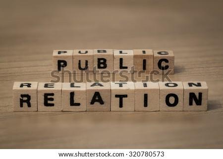 public relation written in wooden cubes on a desk - stock photo