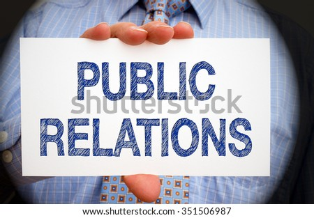 Public Relations - Manager holding white card with blue text - stock photo