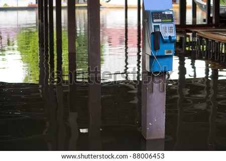 Public telephone booth in a flooded garage - stock photo