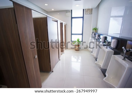 Public toilet with pissoirs and booth - stock photo