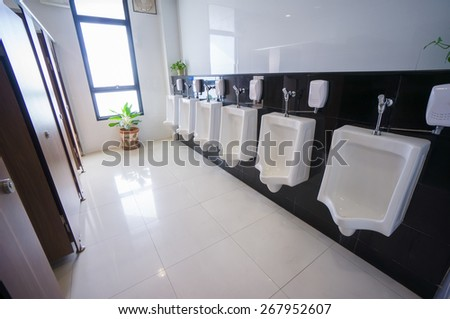 Public toilet with pissoirs on wall - stock photo