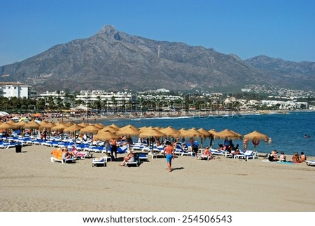PUERTO BANUS, SPAIN - SEPTEMBER 14, 2009 - Holidaymakers relaxing on the beach, Puerto Banus, Marbella, Costa del Sol, Malaga Province, Andalusia, Spain, Western Europe, September 14, 2009. - stock photo