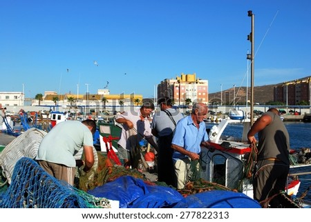 PUERTO DE LA ATUNARA, SPAIN - JULY 7, 2009 - Fishermen sorting their fishing nets on the dockside, Puerto de la Atunara, Costa del Sol, Cadiz Province, Andalusia, Spain, July 7, 2009. - stock photo