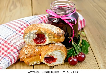 Puff bun with jam, a jar of cherry jam, cherries with leaves, a napkin on a wooden boards background - stock photo