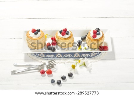 Puff pastries with vanilla-icecream and cream, blueberries and raspberries - stock photo