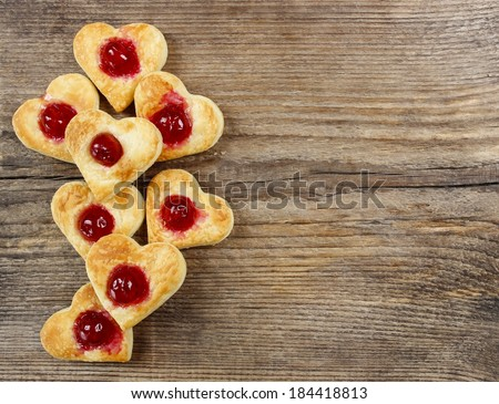 Puff pastry cookies in heart shape filled with cherries. Copy space - stock photo