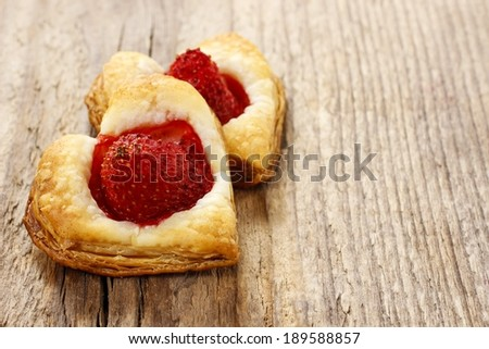 Puff pastry cookies in heart shape filled with strawberries. Copy space - stock photo