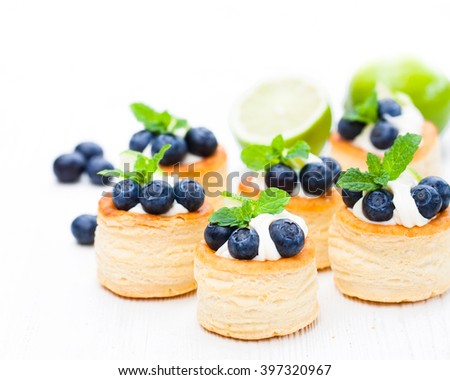 puff  pastry stuffed with soft cream cheese and blueberry with lime on white background  - stock photo