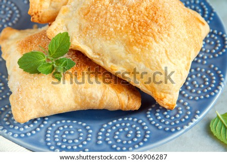 Puff pastry with sugar and mint close up on blue plate - stock photo