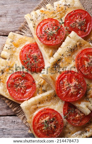 Puff pastry with tomato and cheese on the table close-up vertical. top view  - stock photo
