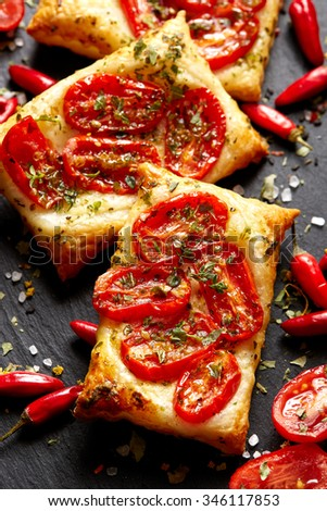 Puff pastry with tomatoes and herbs. Delicious vegetarian appetizer - stock photo